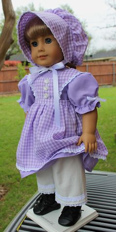 This outfit has been made to fit 18 dolls like American Girl. American Girl Kirsten thinks this outfit will be perfect for her birthday celebration! The dress is made from a lilac cotton fabric. It closes in the back with three buttons and loops. The pinafore is made from a lilac
