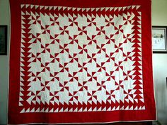 """Red and White Pinwheel Quilt 1860-1880's - Item #2804037.  This is a wonderful old quilt from about 1860 to 1880. It is a red and white pinwheel pattern with a flying geese inside border. The pinwheel and muslin blocks are 4 1/2"""" square. The muslin blocks each have a flower quilted in them with red thread. It is hand quilted with 14 to 16 stitches per inch. It has a cotton batting. It is in excellent condition with no holes or stains or fading.  Available for purchase."""