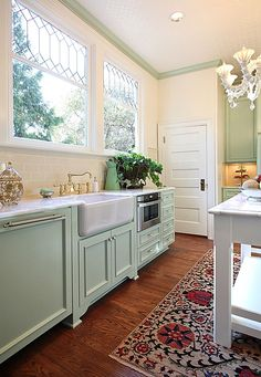 love the wood floors and painted cabinetry, along with windows instead of overhead cabinets
