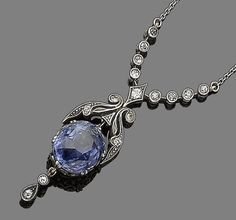 A sapphire and diamond pendant necklace, circa 1900  The cushion-shaped sapphire suspended from a millegrain-set single-cut diamond surmount of scrolling design, terminating in two similarly-cut diamonds, mounted in silver and gold, to a later trace-link backchain, length 54.0cm