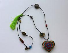 Collar con corazón de madera con mota color verde, listón negro, piedras de colores y dijes en oro viejo. #LovitMx