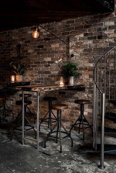 dark bronze bar interior with exposed brick wall, sherwin williams sealskin, dark bronze, dark brown, blackish-brown, brownish-black, warm black, exposed concrete floor, brick wall, metal stools, rustic industrial interior
