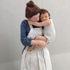 """Miniature doll version of Mary Cassatts's work titled """"Motherhood"""". Porcelain, fabric, and oil paint."""