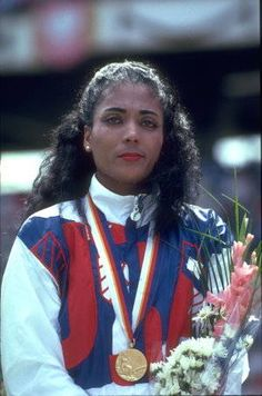 """Florence Griffith Joyner """"Flojo"""" (Dec. 1959 -Sept. 1998)  dazzled the world at the 1988 Olympics with gold medal wins in the 100 meter, 200 meter, & 4x100 meter relay, plus a silver. Flo-Jo almost won a place on the 1980 Olympic team. She married 1984 Olympic gold medal triple jumper Al Joyner in 1987.  She retired from sports in 1989, appearing as an actress, making a fitness video, and writing children's books. She died after a heart seizure in 1998."""