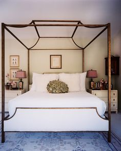 A canopy bed with white linens.