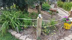 When my doggies wouldn't stay out of the flower bed, I came up with this fence made out of 6 x 6's and rope. The flowers are still viewable and it actually kept them out of the garden....most of the time ;-)