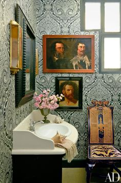 A Nina Campbell for Osborne & Little wallpaper lines a bath; the mirror is 17th-century Spanish, and the portraits date from the 17th and 19th centuries.