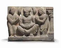 "A GRAY SCHIST RELIEF WITH SIDDHARTHA AND DEVOTEES GANDHARA, 2ND/3RD CENTURY Siddhartha seated in ""royal ease"" with his ankles crossed wearing in a voluminous sanghati and adorned with the jewels of a prince, backed by a nimbus flanked by the boughs of a tree above, a devotee on either side presenting fruit, a column with a foliate capital at far right 13 ¼ in. (33.7 cm.) wide"