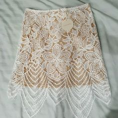 Gorgeous Brand new white lace skirt Never worn because it was too small for me. Beautiful lace details with nude underlining skirt attached underneath. White zipper on the side. Size large but runs small. More like a size small or small medium. Not For Love and Lemons but looks identical to it. For Love and Lemons Skirts Mini