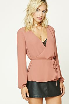 A crepe woven blouse featuring a wrap front with self-tying laces, a peplum hem, and long cuffed sleeves.