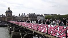 This is the Pont des Arts on the Seine River in Paris, otherwise known as the love-lock bridge. All the locks were removed because the 45 tons of locks were causing the bridge to collapse :( Now it's a street art graffiti bridge with plexiglass in memorial of the locks. While not as cool as when it had the locks, it's still an awesome place!
