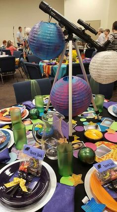 Galactic Starveyors VBS-themed table features ideas from several other Pinterest boards (push light planets, painted paper lanterns planets and Space Junk favors) as well as net and glitter stars from 99 cent store and felt circles for pops of color.