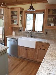 Ideas to update an oak kitchen by adding glass to the solid doors. Shown with granite top and apron front sink. Photo via Zillow, design by Robert Adam Dorn