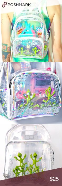 👽Alien Backpack👽 Aliens R Watchin' Backpack don't worry BB, someone is out there watchin' yer back. This adorbz mini backpack is the cutest way to bring all yer essentials for a voyage to the motherland. Featurin' a dope clear construction so everyone can see what ya bring on the spaceship and trippy hologram trim. A roomy interior, dual side slip pockets, front pouch and top zip around closure make this backpack exxxtra extraterrestrial with AMAZING holographic stars and 'lil alien bodies…
