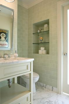Match a vanity to the wall tile's color, then add contrast via the floor and counter. I can't get enough of the combination of soothing greens with gray and white marble in this elegant bathroom.