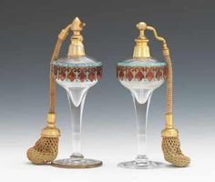 """A Pair of French Glass and Enamed Bronze Perfume Atomizers Glass atomizers decorated with champlevé enamel collars in blue and red; atomizer tops similar but not identical. One bottle stamped """"Made in France"""" on brass base mounting."""