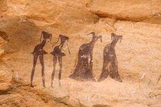 Art rupestre de Tassii n'Ajjer, Algérie. Des hommes en pagne et des femmes en habits complet. Les visages, comme d'autres peintures, ont été délavés par le temps. (TARA)