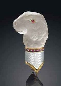 PROPERTY OF A LADY OF TITLE: A JEWELLED TWO-COLOUR GOLD-MOUNTED, GUILLOCHÉ ENAMEL AND ROCK CRYSTAL CANE HANDLE BY FABERGÉ, WORKMASTER MICHAEL PERCHIN, ST PETERSBURG, 1899-1903. Stylistically carved as the head of a hare, set with cabochon ruby eyes, the mount enamelled in translucent pearl white enamel over a wavy guilloché ground, the upper border set with rose cut diamonds and rubies, the lower border cast with green gold laurel band.