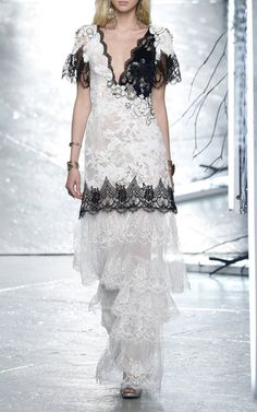 This **Rodarte** gown is rendered in delicate velvet lace and features a deep v-neck with short lace flutter sleeves, tonal hand embroidered flower details at the bodice, and a fit-and-flare design with a layered floor length hem.