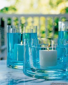 Fire & Water Centerpiece - 2 glass vases, tinted water & candle via martha stewart. This illuminating centerpiece can be created by placing a glass vase inside another that is slightly larger, and filled with tinted water. Water Centerpieces, Simple Centerpieces, Baby Shower Centerpieces, Wedding Centerpieces, Wedding Decorations, Centerpiece Ideas, Graduation Centerpiece, Wedding Ideas, Wedding Reception