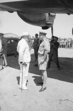 PM Winston Churchill talks to his son, Captain Randolph Churchill, at a North African airfield under the wing of an aircraft following the end of the Desert War/February 1943.