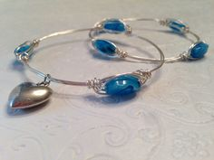 Handmade stackable bangle in non tarnish silver wire with Czech glass beads and silver plated heart charm.  www.etsy.com/shop/patriciaenterprises