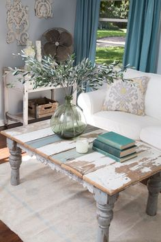 Fixer Upper Host Joanna Gaines staged the newly painted living room with bright and feminine, yet rustic furniture and accessories, making the room feel cozy. A coffee table made from reclaimed wood helps create a French country style, as seen on HGTV's Fixer Upper. (detail)