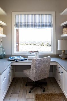 Facing white stacked shelves flank a window dressed in a blue striped roman shade positioned above a white u-shaped desk fitted with a white shaker cabinets and a gray quartz countertop seating a leopard print wingback task chair placed on wood like floor tiles.