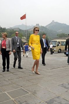 Queen Mathilde looking cool in her cat-eye sunglasses and her bright yellow recycled Natan dress, as she enjoys some sightseeing at the Great Wall of China on her and King Philippe's fourth day in China.