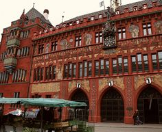 BASEL, SWITZERLAND This is market square . I have bought fruit & flowers here. The red building is unusual . The clock plays music every hour .