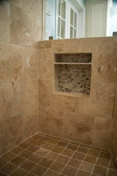 This glass enclosed shower features large neutral wall tiles paired with brown square floor tiles. Brown mosaic tiles are positioned behind a small built-in shelf, providing a perfect spot for storing shower essentials. Mosaic Bathroom, Mosaic Tiles, Wall Tiles, Small Toilet, Built In Shelves, Glass Shower, Bathroom Shelves, Foot Rest, Modern Decor