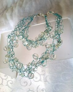 Pure, chunky crystal quartz rounds and nuggets are woven into ice-blue crocheted wire.  I enjoyed making the bracelet so much, I decided to make a matching necklace.  Both bracelet and necklace are securely fastened with strong magnetic clasps.  Crystal Ice from Stop Fighting the Clasp.