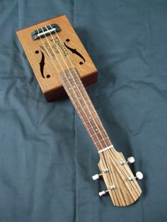 Vintage cigar box soprano ukulele. Hand carved cherry neck with maple stripe. Zebrano head veneer. Bone nut and saddle. Freshwater mussel shell dot inlays. Grover tuners. Piezo pickup. Made by the Filthy Don guitar co.