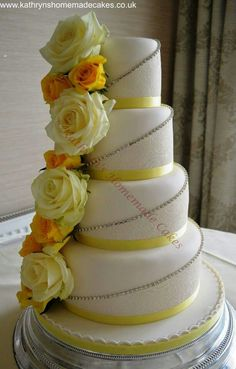 4 tier wedding cake with cake lace and diamanté trim. Fresh Roses add the finishing touch