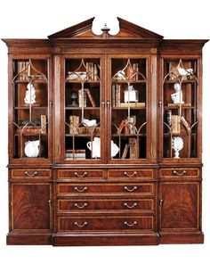 The Jonathan Charles 493156 China/Display Cabinet comes in Antique Mahogany Medium finish, is from the Buckingham Collection and measures 85.83W x 19.69D x 94.09H inches. This item comes with Individually Glazed Panes-Lighted. George II style mahogany veneered and cross banded china display cabinet, the central section with a broken pediment centred with an urn, the whole with glazed doors with gothic ogee topped glazing bars, adjustable glass inset shelves, and four short and three grad...