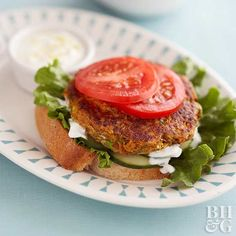 Veggie burgers need not be boring. Season shredded zucchini, carrots, and crushed crackers with green onions and top with a creamy garlic yogurt sauce to create this Mediterranean-inspired vegetarian burger idea. Carrot Zucchini Recipe, Carrot Recipes, Veggie Recipes, Diet Recipes, Cooking Recipes, Veggie Meals, Veggie Sandwich, Veggie Burgers, Vegan Sandwiches