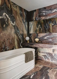 This bold art deco beach villa bathroom has a metal trough tub, stainless steel fixtures, and bold stone pattern blanketing the room.