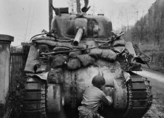 Assessing the Damage to an M4 Sherman - An American soldier checks out the gouge that a German armor-piercing projectile made on the front hull of this M4 Sherman medium tank.