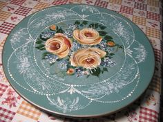 Lace, stroke roses, rosebuds and forget-me-nots have been painted on this placemat or lazy Susan by a name I can't quite decipher (T Long?)