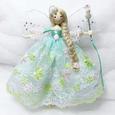Meet Little Miss Lottie, a beautiful handcrafted fairy doll that will adorn any room in your home! She is approximately 7 inches tall from the tip of her toes to the top of her head and hangs from a silver thread. She wears a very pale aqua tulle lace dress embroidered with pink and