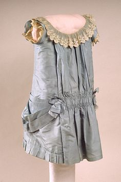 circa 1885.  Child's dress made of powder blue silk with a white, needlerun lace band around the short, circular neckline, which was made (m...