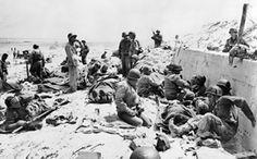 UTAH BEACH Des blessés américains attendent d'être soignés à l'abri d'un mur, à Utah Beach, le 6 juin 1944