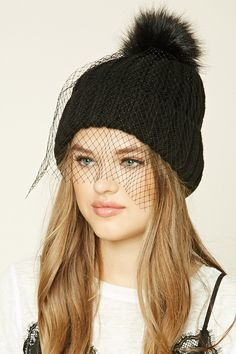 A ribbed knit beanie featuring a veil, a faux fur pom-pom, and a fold-over design.