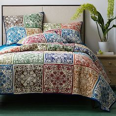 Our Gosford patchwork quilt is a contemporary take on traditional block prints, displaying squares of floral medallions in opulent tones.