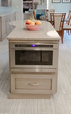 Kitchen Island - Built in microwave, extra storage and prep space, spot for seat on the end, gray stained wood with silestone countertops.