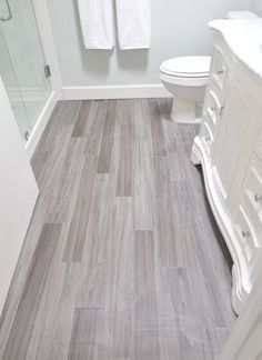 Bathroom floor of vinyl plank budget friendly flooring tiles. These are Trafficmaster Allure in Grey Maple and are installed in a random offset pattern like hardwood flooring. Available @ Home Depot stores Bathroom Renos, Bathroom Flooring, Bathroom Vinyl, Tile Flooring, Modern Bathroom, Bathroom Plumbing, Bathroom Layout, Bathroom Small, White Bathroom