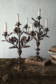 白百合咲かん、教会のキャンドルスタンド-pair brass candle stand マドンナ・リリー、キリスト教において聖母マリアの象徴、白い百合のモチーフが絡むペアの燭台。ひゅるり伸びるステムの線が背景に幾筋の影をもたらす。台座のうねりはフランボボワイヤン-主イエスの聖心を表す燃える心臓周りの炎に見えるし、玉に絡むはいばらの冠然り。低く揺らぐ蝋燭の光が等しく照らしたはず、壁を、人を、その空間を。推定19世紀半ば、フランス中南部リヨン近郊のアンティーク屋さんより。蝋燭6本が付属しており、真鍮に鑞の付着物が御座います。