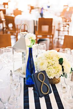 The navy and white tablecloth pairs well with the cobalt blue bottle and the indigo blue table number. Source: The Hostess with the Mostess. #centerpiece #navyandwhite