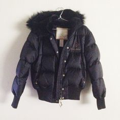 NWOT Baby Phat quilted puffer jacket/vest Never worn Baby Phat quilted puffer jacket/vest.  - Detachable hood (snap off) & sleeves (zippered) w/ signature cat pull tabs - Fur lined hood & collar - Fur trim on hood - Full gold-colored snap & zipper closure w/ cat pull tab - Zipper pockets w/ cat pull tabs - Knit trim around sleeves & hem - Gold-colored cat stitched on back - Fully lined  Shell: 100% nylon Lining: 100% polyester Fill:  60% goose down, 40% water fowl feather Trim: 100% natural…