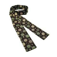 This is a handsome brown silk 50s bow tie with a white and green print of discs made of various sized rectangular tiles. The tie is adjustable for